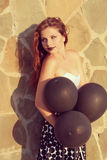 Girl with black balloons Stock Image