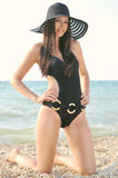 The girl in a black bathing suit. A beautiful girl in a bathing suit, a hat, resting on the sea stock photo