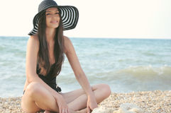 The girl in a black bathing suit. A beautiful sexy girl in a bathing suit, a hat, resting on the sea Stock Image
