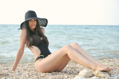 The girl in a black bathing suit. A beautiful girl in a bathing suit, a hat, resting on the sea stock images