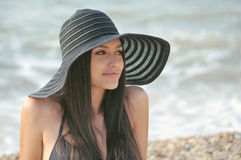 The girl in a black bathing suit. A beautiful girl in a bathing suit, a hat, resting on the sea royalty free stock photo