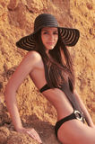 The girl in a black bathing suit. In black hat on a background of orange rocks Royalty Free Stock Photography
