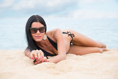 Girl in a black bathing suit lying on the sand Stock Photography