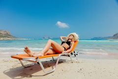 Girl in black bikini and with hat on Balos beach. Young redhead girl in black bikini and with hat lying down on lounger on Balos beach, west Crete, Greece royalty free stock photography