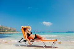 Girl in black bikini and with hat on Balos beach. Young redhead girl in black bikini and with hat lying down on lounger on Balos beach, west Crete, Greece royalty free stock image