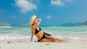 Girl in black bikini and with hat on Balos beach. Young redhead girl in black bikini and with hat on Balos beach, west Crete, Greece. Summertime season vacation royalty free stock images