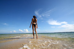 Girl in black bikini walking on the white beach Royalty Free Stock Images