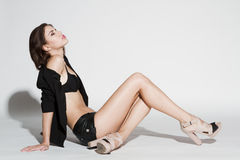 Girl in black blazer and leather shorts. Sitting on white background Royalty Free Stock Photography