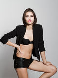 Girl in black blazer and leather shorts. Against white background Stock Photo