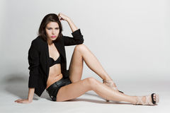 Girl in black blazer and leather shorts. Sitting on white background Stock Photos