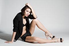 Girl in black blazer and leather shorts. Sitting on white background Stock Images