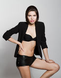 Girl in black blazer and leather shorts. Against white background Stock Image