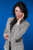 Girl in a black blouse. Girl in a striped jacket on a blue background Stock Image
