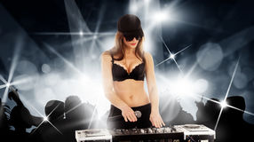 Girl in the black bra with the mixer. Girl DJ in a cap with the mixer and microphone in the dark glasses and black bra playing music on a disco party stock photography