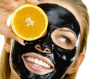Free Girl Black Carbo Mask On Face Holds Orange Fruit Royalty Free Stock Images - 161855569