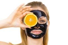 Free Girl Black Carbo Mask On Face Holds Orange Fruit Royalty Free Stock Photo - 164447645
