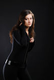 Girl in black catsuit against the dark background. Stock Photography