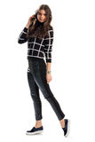 Girl in black checkered pullover. Skinny fit pants and shoes. Cute model wears autumn clothes. Leather and cotton Stock Photo