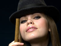 Girl in black with a cigarette. Graceful lady in a hat and a cigarette in a hand Royalty Free Stock Photo