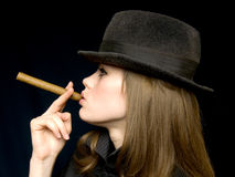 Girl in black with a cigarette in a hand. Graceful lady in a hat and a cigarette in a hand Royalty Free Stock Images