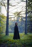 The girl with the black cloak in the forest Royalty Free Stock Photos