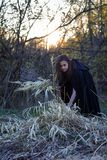The girl with the black cloak in the forest Stock Photo