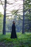 The girl with the black cloak in the forest Stock Photos