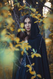 The girl with the black cloak in the forest Royalty Free Stock Image