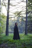 The girl with the black cloak in the forest Royalty Free Stock Photo
