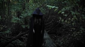 A girl in a black cloak with a hood shows her finger straight, a mystical lady is in a scary park in the evening