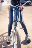 The girl in black clothes the cool bicycle with the vintage camera in a cover a sunlight Royalty Free Stock Image