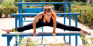 Girl. In black clothes laughing on the bench doing the splits Stock Photos