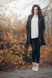 Girl in black coat in autumn in park. Royalty Free Stock Images