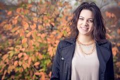 Girl in black coat in autumn in park. Royalty Free Stock Photo