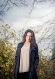 Girl in black coat in autumn in park. Stock Photos