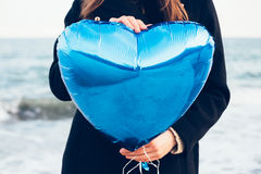 Girl in black coat holding a blue balloon in the shape of a heart Royalty Free Stock Images