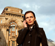 Girl in black coat with mobile phone in the City Stock Photos