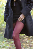 Girl in black coat and red stockings Stock Photo