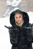 Girl in black coat and snow fall. Pretty girl in black coat posing under the snow fall stock photography
