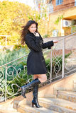 Girl in black coat stand on stairs, autumn season Stock Image