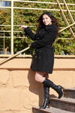 Girl in black coat stand on stairs, autumn season Royalty Free Stock Photography