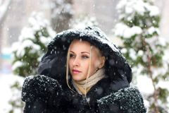 Girl in the black coat under snow fall - close up portrait Stock Photo