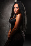 A girl in a black corset. Stylish hairstyle, dreadlocks. Black long hair. Girl with an unusual hairdo. Black long hair. dreadlocks Stock Photo