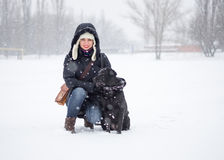 The girl with a black dog on the snowfield Royalty Free Stock Image