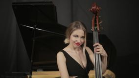 Girl in black dreess playing on the contrabass stock video footage
