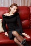 Girl in black dress. Posing on the coach stock image