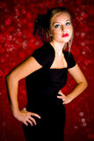 Girl in black dress. Girl wearing a black dress and veil against a red background Royalty Free Stock Image