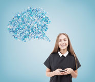 Girl in black dress against blue background. Smiling girl in black dress holding a smartphone and standing against light blue background with blue thought bubble Stock Photo