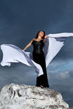 Girl in a black dress on a background of the cloudy sky Stock Image