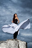 Girl in black dress on a background of the cloudy sky Stock Photo
